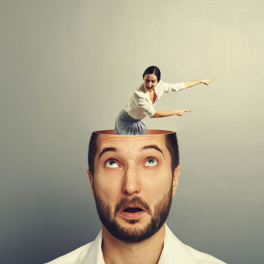 Tiny woman popping out of surprised man's head to tell him what to do. Symbolic representation of how women influence men..