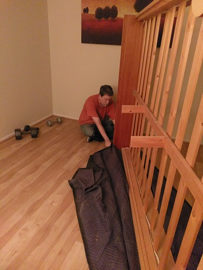 dragging a bedframe using a packing blanket.