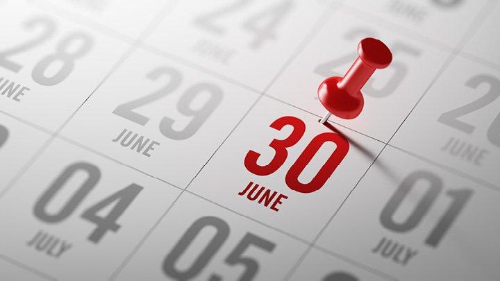 Push pin marking June 30 on calendar