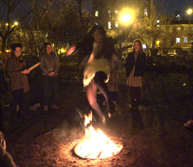 Young woman jumping a fire during Chaharshanbe Suri