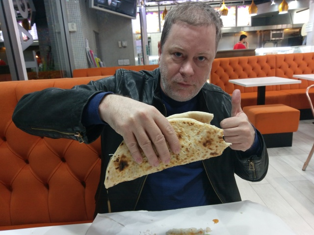 Sitting in a kebab shop in Manchester holding a massive kebab