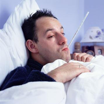 Sick man in bed with thermometer in mouth